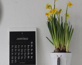 Balts koka kalendārs ar melnām lapām
