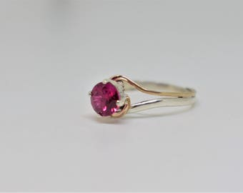 Pink lab created gemstone ring with .925 sterling silver band and 12/20 gold accent. (size 6.5)