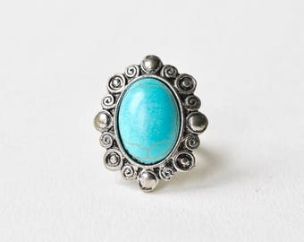 Vintage silver tone oval turquoise swirl statement ring. Oval cabochon faux turquoise, howlite swirl silver tone detail adjustable ring.