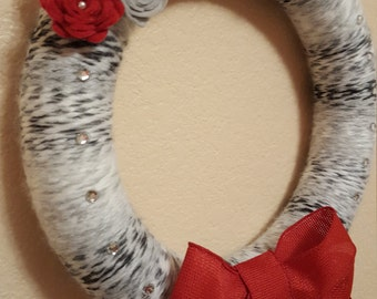 Cozy, winter Christmas wreath with red bow and flowers