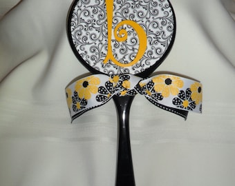 Handcrafted wooden hand mirror. Black base with curly Q print and an initial embellishment.