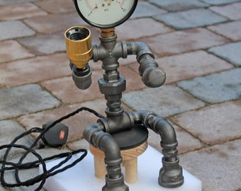 Pipelight figure sat on a simple wooden bench made from industrial pipe fittings. Pressure gauge head edison light bulb.