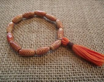 Patterned wood bead bracelet with orange tassel