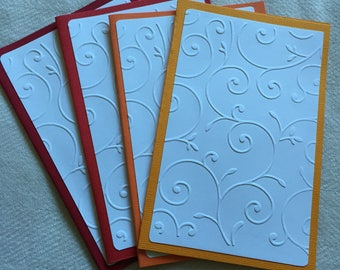 Hand made Embossed note / greetings cards. White elegant swirls pattern on shades of red & orange. (4 cards). CP20