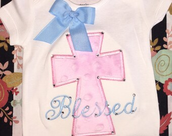 Blessed onesie with a cross applique