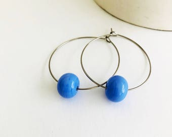 Earrings loops with periwinkle glass beads .