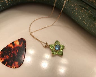 Peridot and blue topaz flower pendant set in 14k yellow gold .