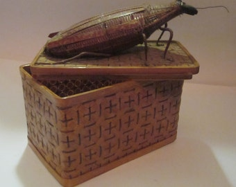 woven rattan and cane box with woven roach attached to the lid