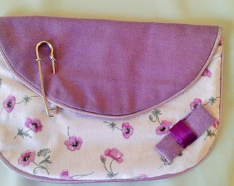 Small purple pouch floral bag has hand