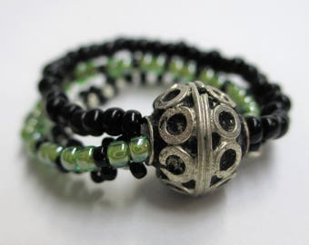 Green, black, and silver multi-strand beaded ring with metal Bali style metal focal bead