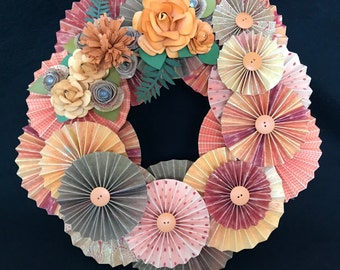 orange and brown paper rosette wreath with three assorted handmade flowers