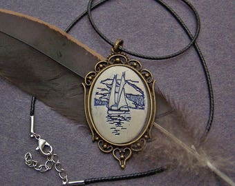 30X40 mm ceramic blue sailboat pendant necklace with a bronze metal setting.