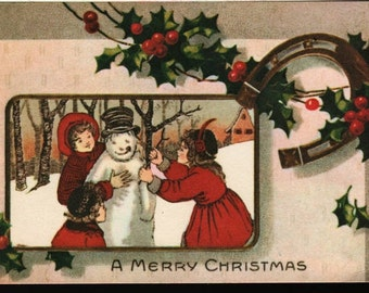 A Merry Christmas + Children with Snowman and Holly- Vintage Postcard
