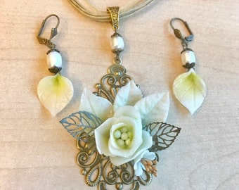 Set in ivory, bronze and antique gold, freshwater pearls and cold porcelain flower