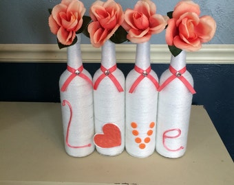 Shimmery White and Coral Yarn Wrapped Wine Bottle Centerpiece with Flowers that Spell Love