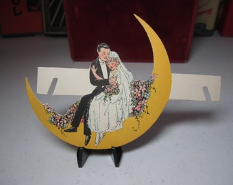 Gorgeous unused art deco die cut fantasy wedding place card 1920's bride and groom sitting inside yellow crescent moon