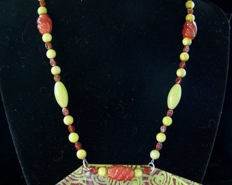 Bold, artistic lime and rust enamel pendant on a complementary beaded necklace w earrings