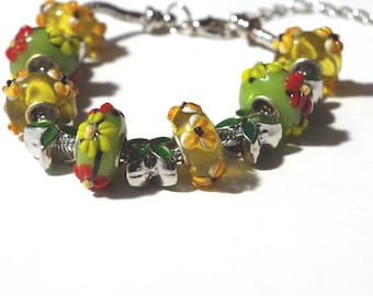 Lovely bracelet made with glass beads with little flower on green background.