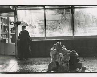 Sad man in rain by store window vintage art photo