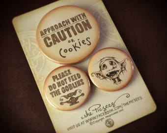 A set of 3 PIN BUTTON BADGES featuring Eric the goblin and some wise warnings that should always accompany the likes of him...by the Picsees