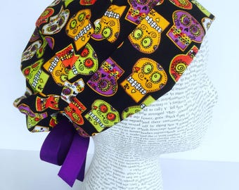 Ribbon Tie Back Scrub Cap scrub hat featuring a black material with red white green orange and purple sugar skulls and a purple ribbon