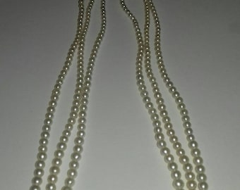 Three strand faux pearl necklace with imperfections.