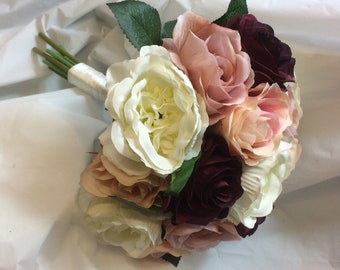 A bridal bouquet of dusky pink, burgundy and ivory roses