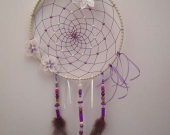 Dream catcher is handmade white, purple and gold, decorated with 3 flowers