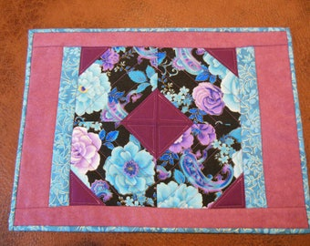 Placemats quilted in purple, aqua,paisley material.   Set of 4
