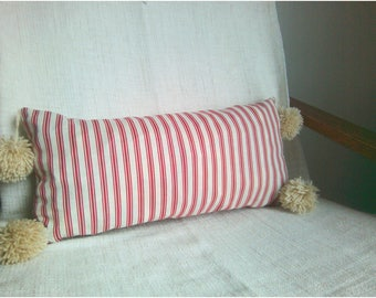 Red and white striped pillow has tassels
