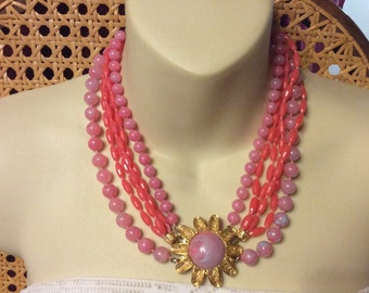 Pink beaded multi strand flower front closure necklace.