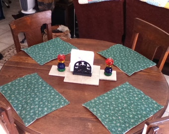 Handmade set of 4 quilted square placemats in green with tiny pink flowers.