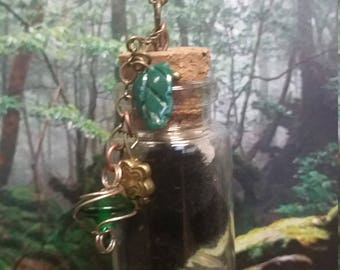 Soot Pendant with 3 contained soots and 2 contained Konpeito candy in corked bottle. Includes a antique brass toned necklace and charms. (G)