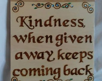 "Inspirational wood burned painted and embellished plaque with the quote ""Kindness when given away keeps coming back"" with vines and leaves"
