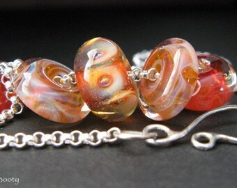 Glass and sterling silver necklace.  Boro lampwork beads, warm fall colors.  Apricot, peach, red and orange. Quality chain. Charmed.