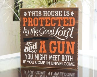 IN STOCK~   This house is protected by the good Lord and a gun 12x12 Solid Wood Sign Choose your hanger