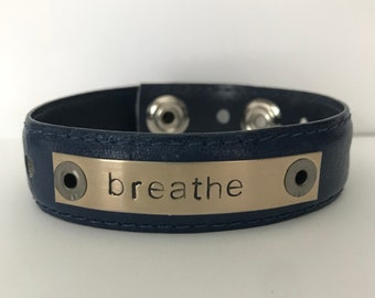 "Thin navy blue belt bracelet cuff with a hand stamped message on a silver blank which reads, ""breathe."""