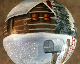 Handpainted ornament with a winter cabin scene