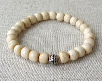 Beaded Stretch Bracelet - Antiqued Bone Beads with a Tibetan Silver Charm