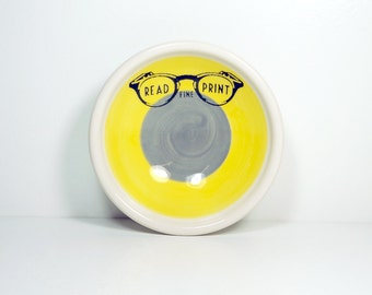 """small dish, with a """"Read Fine Print"""" sign shown here on a color block of yellow & storm, made to order."""