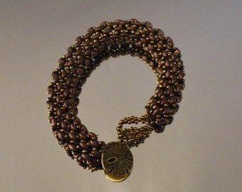 Slinky and smooth burgundy and gold beaded bracelet with a metal sand dollar button for a clasp.