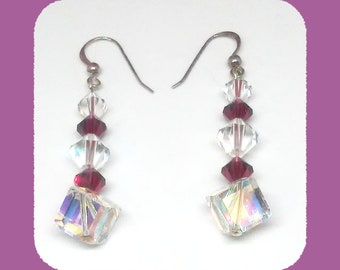 Clear and Garnet colored Swarovski crystal refract the light giving a rainbow of colors in these dangle earrings
