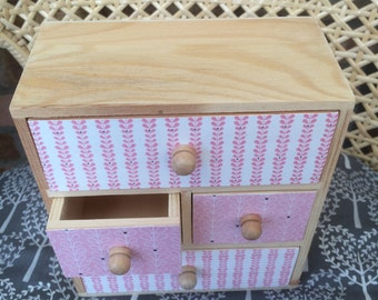 Small four drawer wooden chest.