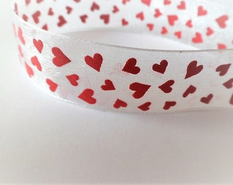 White ribbon with red hearts