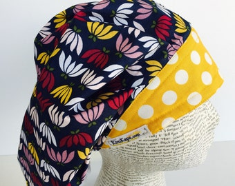 Traditional Bouffant Scrub Cap scrub hat featuring a dark blue material with flowers in pink white and yellow with a coordinating band 2t