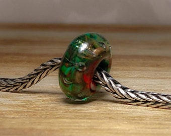 Green and gold with a splash of red. Handmade glass lampwork bead.