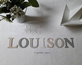 First name, weathered, wooden letters pink, grey and white cement; shabby vibe