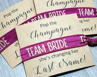 Pop The Champagne She's Changing Her Last Name Hair Tie Favors | Bachelorette Party Favors | Bridesmaid Gift + Favors | Burgundy Wedding