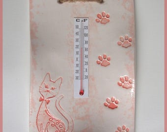 Thermometer ceramic coral red cat on a white background, and cat paws print