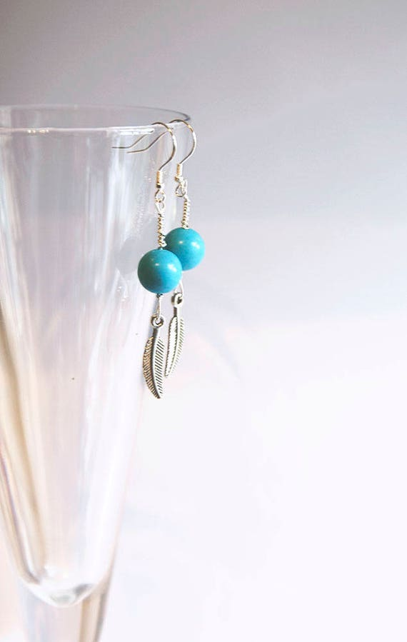 Turquoise bead earrings on sterling silver wire, with Tibetan silver feather charm on sterling silver hooks.